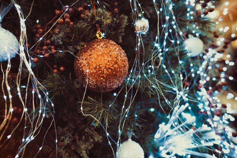 Fin vers le haut de la babiole d'or de paillettes accrochant sur décoré de l'arbre de Noël de lumières Décorations de Noël sur un photographie stock