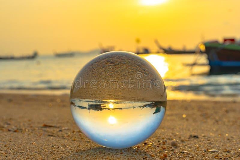 fin vers le haut de la boule de verre cristal mise sur la plage photo stock