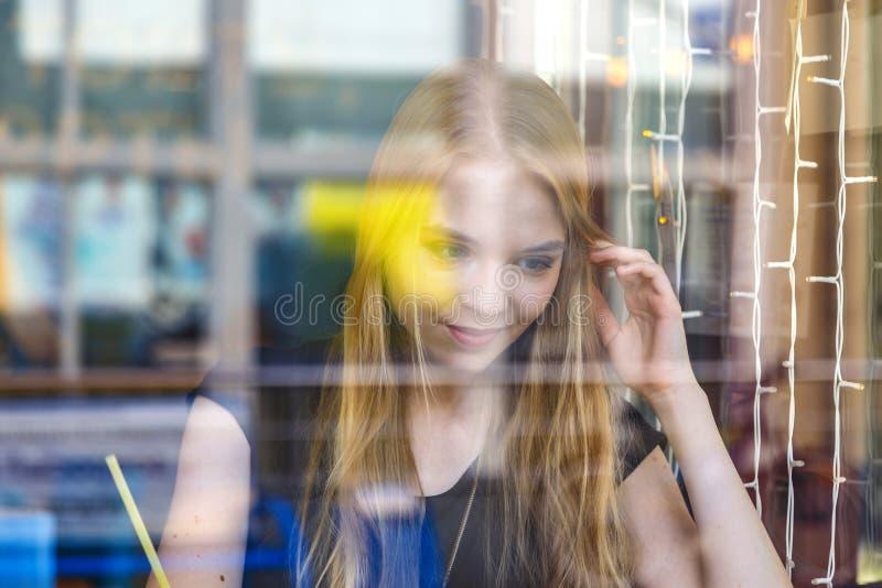 Fin vers le haut de la femme blonde de sourire de fenêtre de jet de vue faisant des notes avec le crayon photos libres de droits