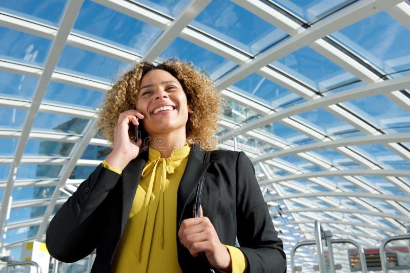 Fin vers le haut de la femme d'affaires de sourire d'afro-américain parlant sur le téléphone portable image libre de droits