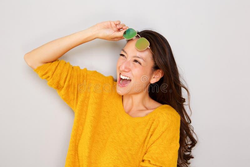 Fin vers le haut de la jeune femme asiatique élégante riant avec des lunettes de soleil sur le fond gris photo stock