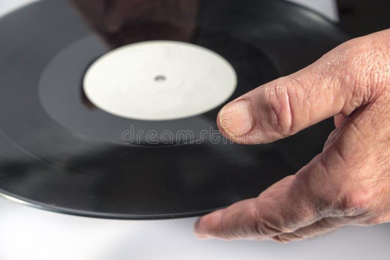 fin vers le haut de la main de l'homme tandis que prises un disque vinyle photos libres de droits