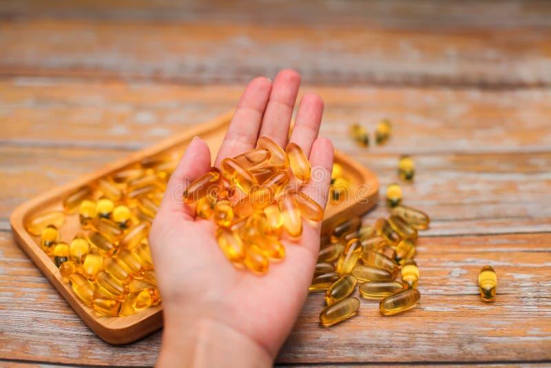 Fin vers le haut de la main femelle tenant des capsules d'or avec le complément alimentaire ou les vitamines photo stock