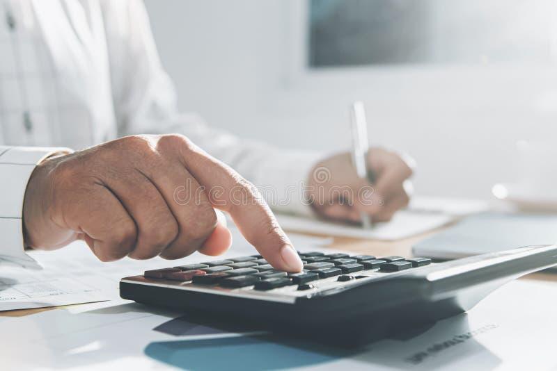 fin vers le haut de la main de la femme d'affaires travaillant au bureau dans le bureau et à l'aide de la calculatrice et de l'or image libre de droits