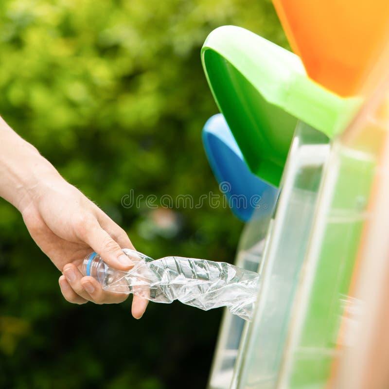 Fin vers le haut de la main mettant la bouteille en plastique dans la poubelle photographie stock