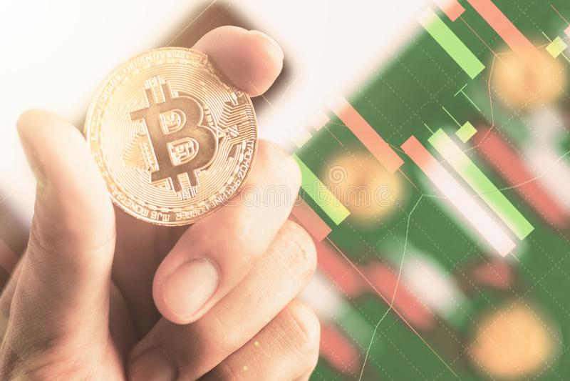 Fin vers le haut de la main tenant le bitcoin avec le diagramme de chandelier de fond image libre de droits