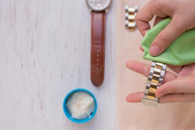 Fin vers le haut de nettoyer la montre moderne avec le tissu de microfiber images stock