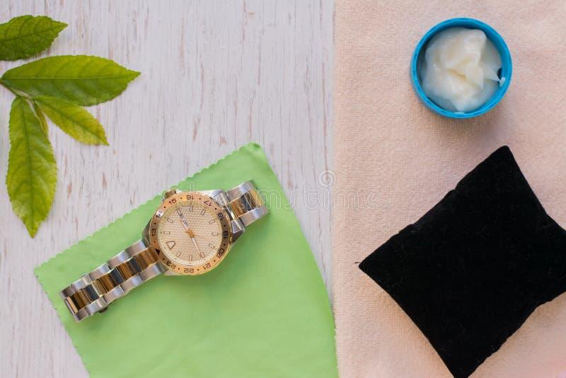 Fin vers le haut de nettoyer la montre moderne avec le tissu de microfiber photographie stock