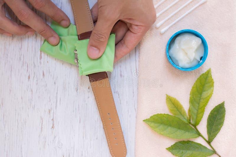 Fin vers le haut de nettoyer la montre moderne avec le tissu de microfiber photographie stock libre de droits