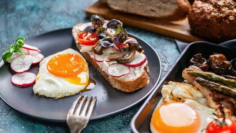 Fin vers le haut de petit déjeuner fait maison délicieux Fried Eggs, de sandwich, de fromage, de légumes, de champignons, de pain image libre de droits