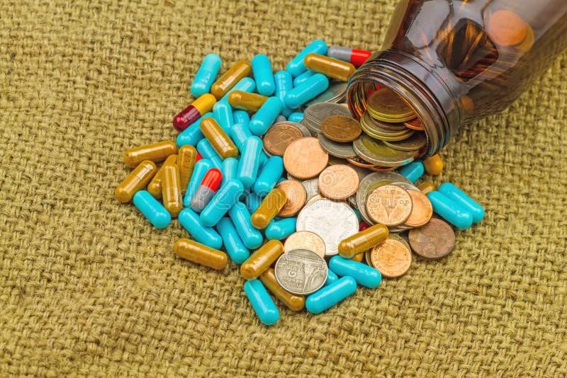 Fin vers le haut de pile de médecine dans la pile brune de bouteille et de pièce de monnaie sur SA photos stock