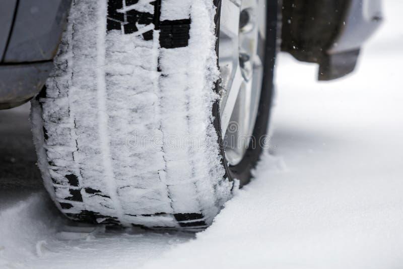 Fin vers le haut de roue de voiture de détail avec le nouveau protecteur noir de pneu en caoutchouc sur la route couverte par nei photos stock