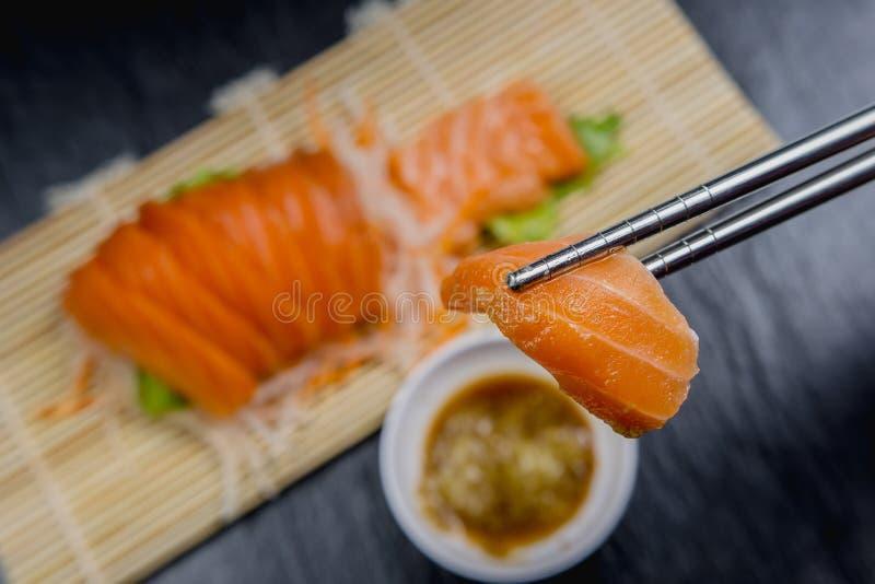 Fin vers le haut de salade figée de sashimi saumoné frais du plat en bambou, nourriture japonaise photos stock