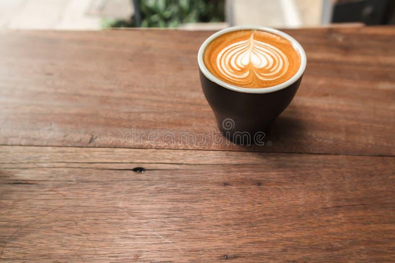 Fin vers le haut de tasse de café noir avec l'art de latte de forme de coeur photographie stock