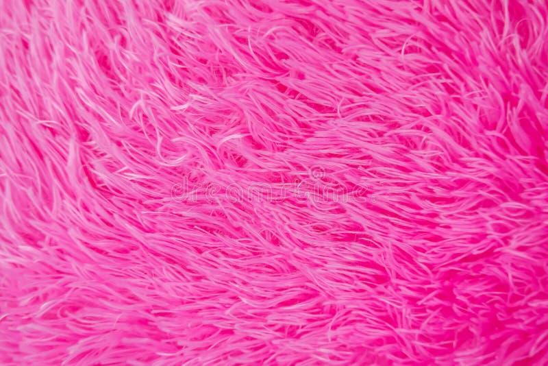 Fin vers le haut de texture hirsute ou de tapis de fourrure artificielle de rose photos stock