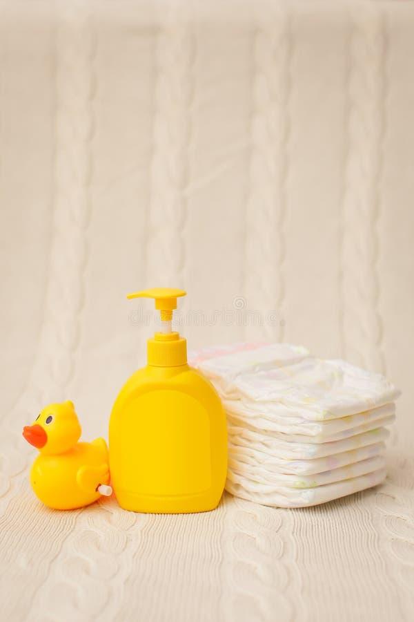 Fin vers le haut des articles d'hygiène de bébé pile des couches-culottes, du savon liquide et du canard jaune sur le plaid beige image libre de droits