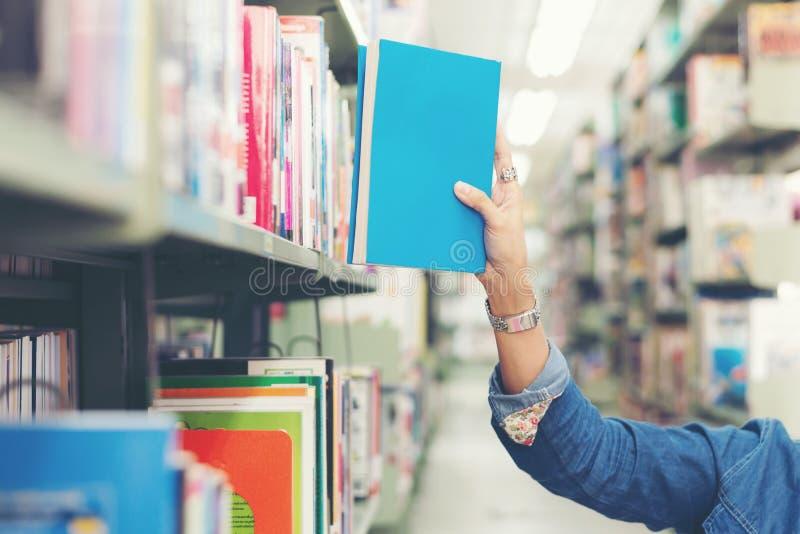 Fin vers le haut des femmes d'?tudiant de main trouvant le livre pour lire dans la biblioth?que image libre de droits