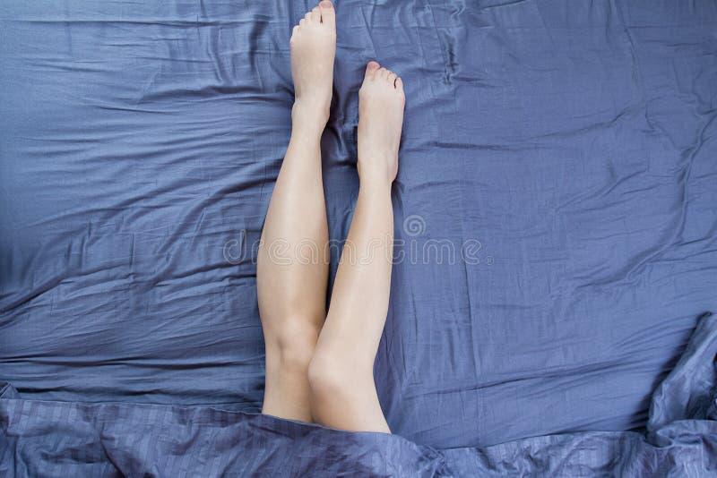 Fin vers le haut des jambes de femme dans le lit sous la couverture Belles jambes ras?es apr?s traitement de soins de la peau de  photographie stock libre de droits