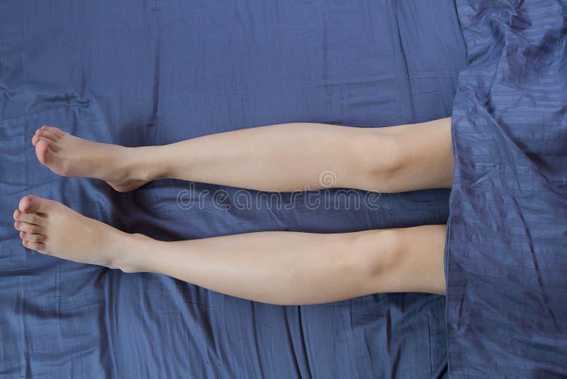 Fin vers le haut des jambes de femme dans le lit sous la couverture Belles jambes ras?es apr?s traitement de soins de la peau de  photos libres de droits