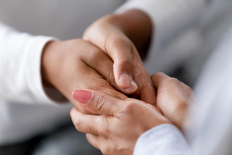 Fin vers le haut des mains de soin d'enfant de participation de mère d'Afro-américain image libre de droits