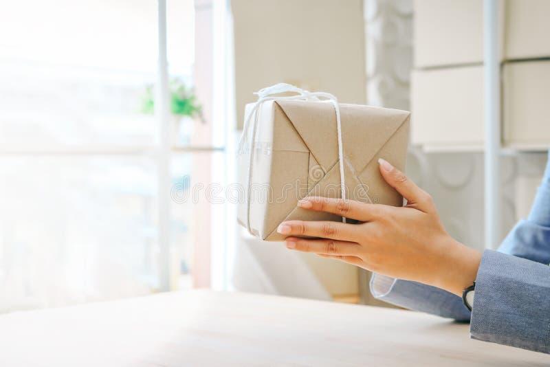 Fin vers le haut des mains jugeant le boîte-cadeau enveloppé avec le papier d'emballage image libre de droits