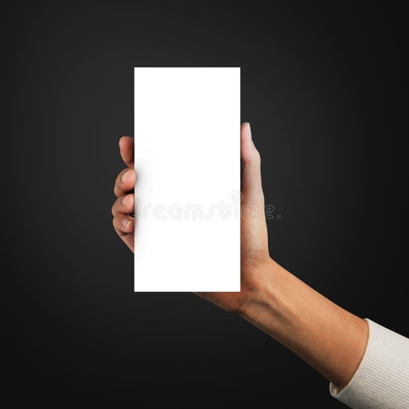 Fin vers le haut des mains tenant le calibre vide de papier de la brochure a4 trois sur un fond gris images stock