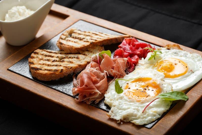 Fin vers le haut des oeufs de petit déjeuner et le jamon et le fromage de pain grillé photo stock