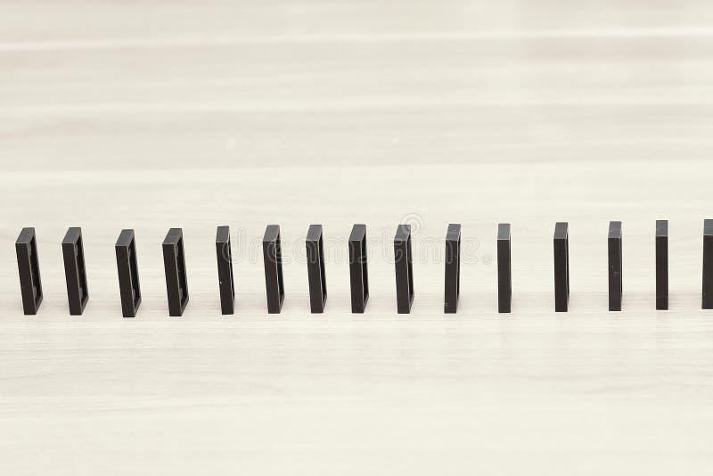 Fin vers le haut Des puces de domino sont construites dans une rangée sur l'homme d'affaires de bureau photos stock
