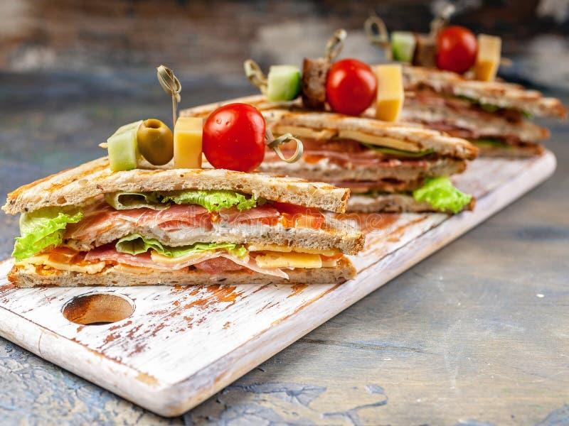 Fin vers le haut des sandwichs frais à tranche avec du boeuf, les tomates et la salade verte Petit d?jeuner ou d?jeuner tradition photos libres de droits