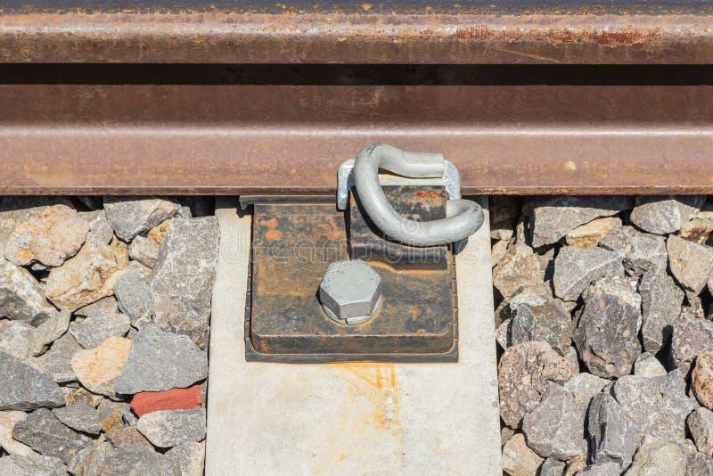 Fin vers le haut des vis rouillées et des attaches en acier d'écrou sur la vieille voie de chemin de fer image stock