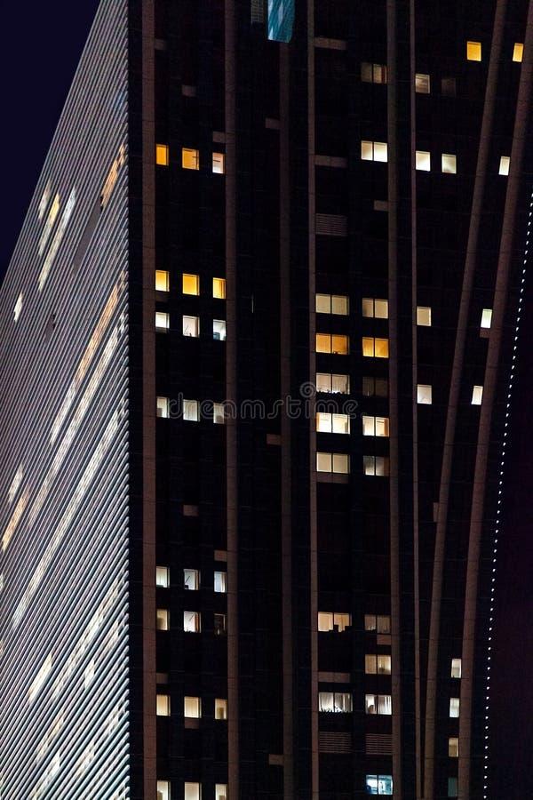 Fin vers le haut du bâtiment moderne en verre de local commercial avec l'illumination de nuit photographie stock libre de droits
