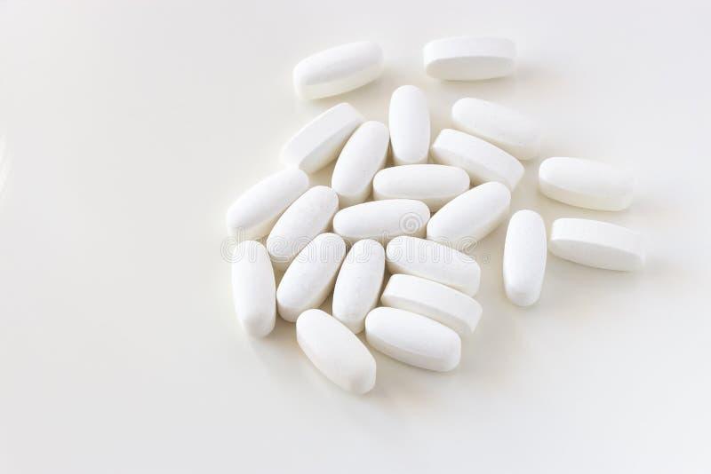 Fin vers le haut du carbonate de calcium ou la vitamine blanche et les comprim?s min?raux de pilules d'isolement sur le fond blan photo libre de droits