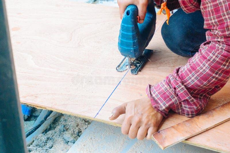 Fin vers le haut du charpentier asiatique d'homme à l'aide des scies électriques pour couper le grand panneau du bois dans un cha photo stock