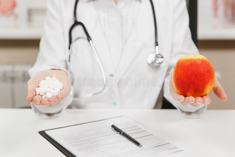 Fin vers le haut du docteur féminin cultivé s'asseyant au bureau, tenant la bouteille avec les pilules blanches dans la paume, po images stock