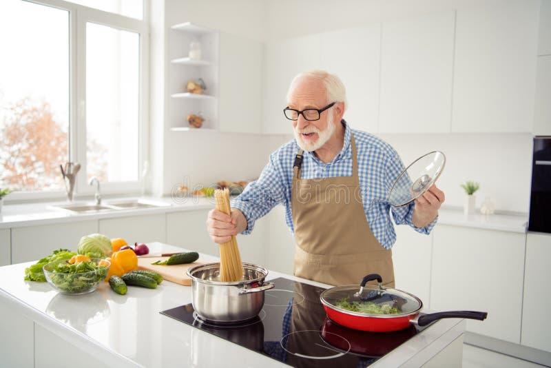 Fin vers le haut du gris de photo d'une chevelure il son il cuisinier de grand-papa faisant frire le processus délicieux occupé d photo stock