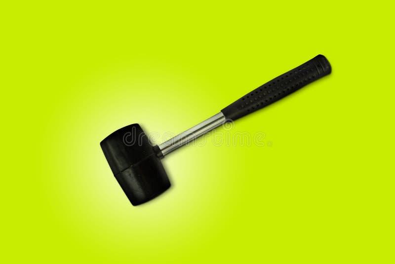 Fin vers le haut du maillet en caoutchouc noir d'isolement sur le fond vert clair Le marteau en caoutchouc est un outil de constr photographie stock libre de droits