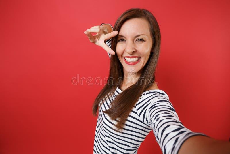 Fin vers le haut du selfie tiré de la jeune femme joyeuse de sourire dans des vêtements rayés occasionnels montrant le signe de v photos libres de droits