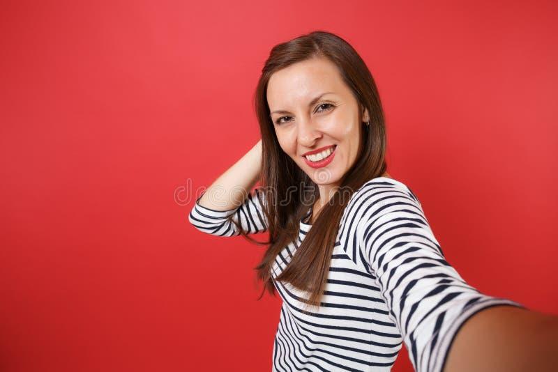 Fin vers le haut du selfie tiré de la jeune femme renversante attirante dans des vêtements rayés mettant la main sur la tête d'is images libres de droits