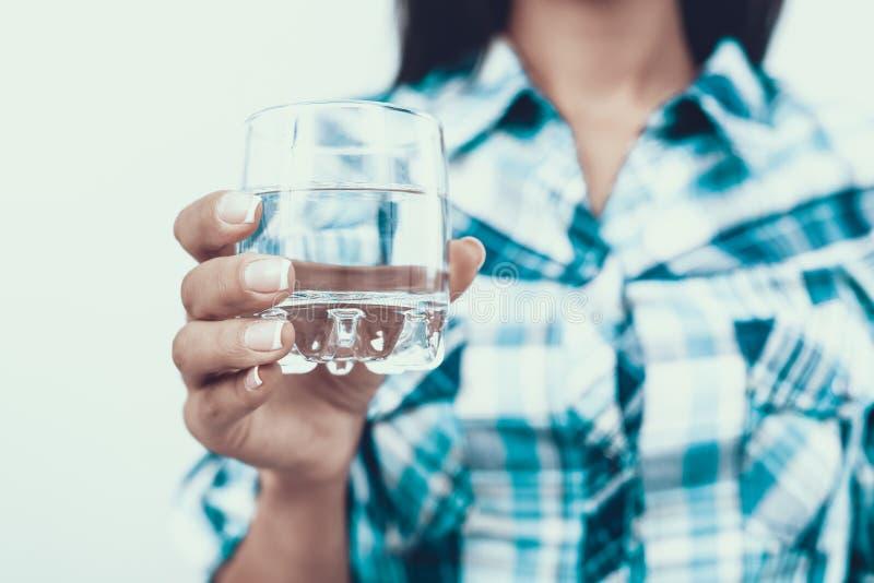 Fin vers le haut Femme dans la chemise tenant le verre de l'eau photo stock
