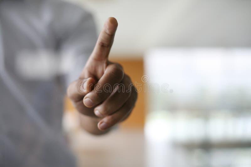 Fin vers le haut Homme africain d'affaires tenant le doigt sur l'écran tactile image stock