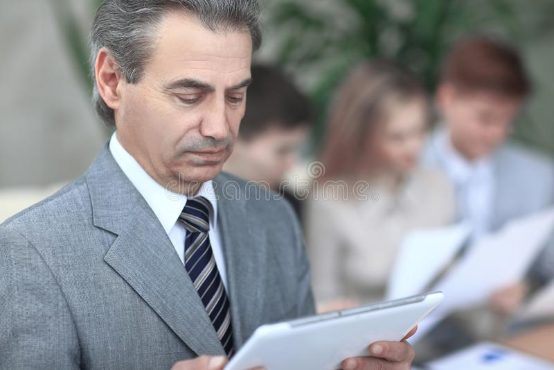 Fin vers le haut homme d'affaires moderne regardant l'?cran num?rique de comprim? photo sur le fond brouill? de bureau photographie stock