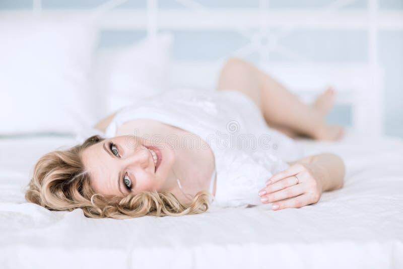 Fin vers le haut jeune femme enceinte heureuse se trouvant sur le lit image stock