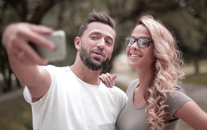 Fin vers le haut jeunes couples de sourire prenant le selfie en parc de ville image stock