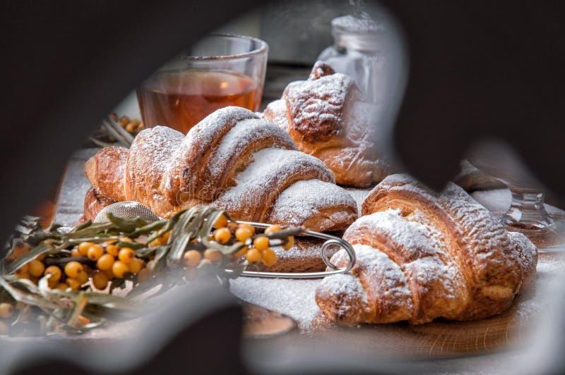 Fin vers le haut Jour du `s de Valentine Petit déjeuner romantique avec les croissants français et le thé chaud Vue par un écran  photo stock