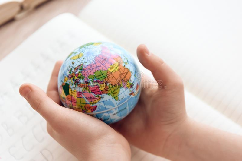 Fin vers le haut L'enfant tient le petit globe dans des mains photos libres de droits