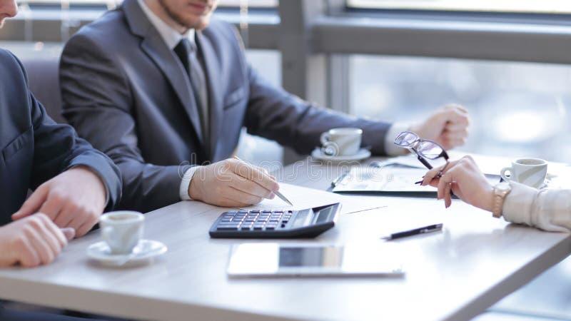 Fin vers le haut l'homme d'affaires v?rifie les donn?es financi?res utilisant une calculatrice photo stock