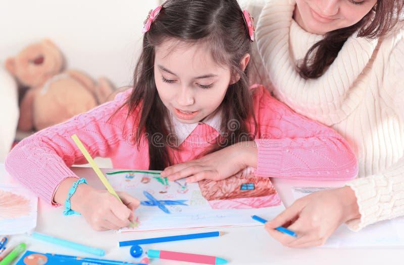 Fin vers le haut la maman aide sa petite fille à dessiner une photo images libres de droits