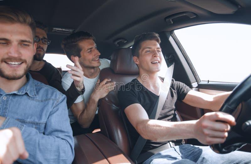 Fin vers le haut les bons amis conduisent dans la voiture image stock