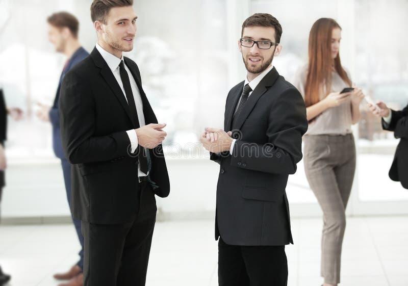 Fin vers le haut les collègues d'affaires discutent des problèmes commerciaux se tenant dans le bureau photographie stock