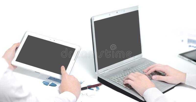 Fin vers le haut les employés utilisent un ordinateur portable et un comprimé pour le travail images stock